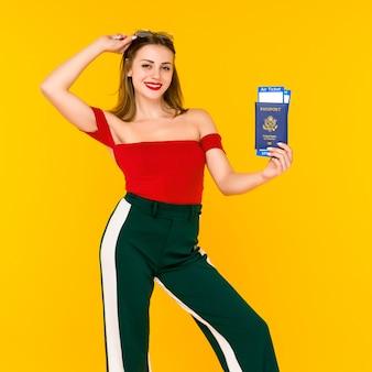 Retrato de una mujer joven feliz con billetes de viaje y pasaporte aislado sobre fondo amarillo. centrarse en el pasaporte.