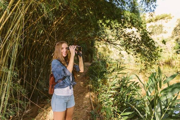 Retrato de una mujer joven feliz con binoculares de pie en el bosque