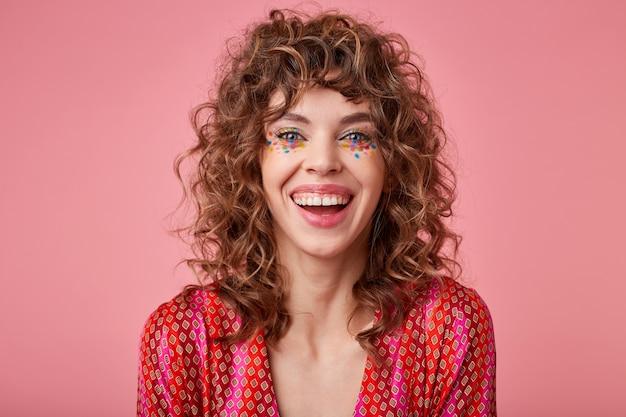 Retrato de mujer joven feliz con cabello rizado, sonríe ampliamente, vistiendo ropa a rayas, aislado. concepto de emociones positivas