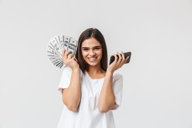 Retrato de una mujer joven y feliz casualy vestida aislado en blanco, mostrando billetes de dinero, mediante teléfono móvil
