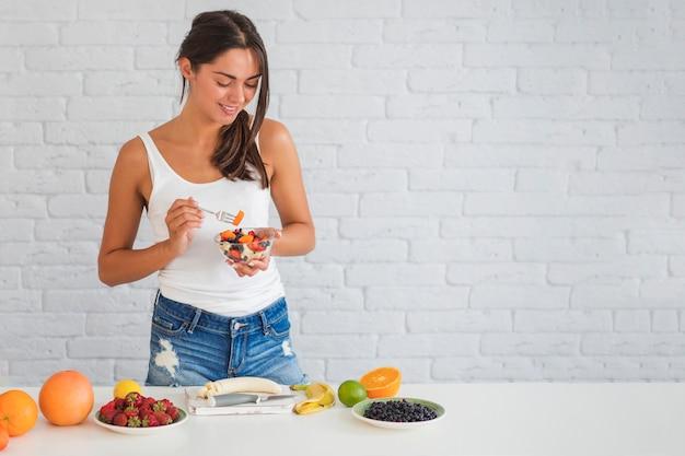 Retrato de mujer joven feliz comiendo ensalada de fruta fresca hecha en casa