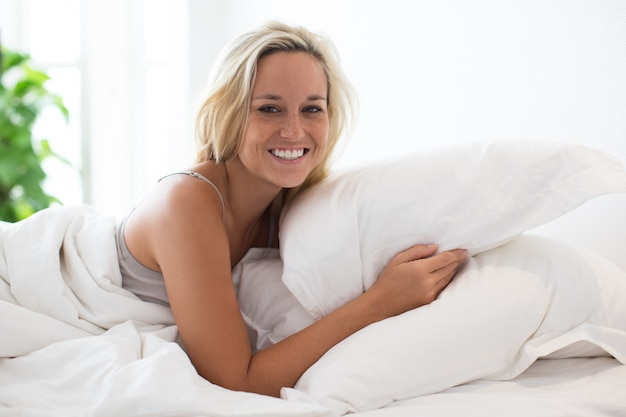 Retrato de mujer joven feliz descansando en la cama