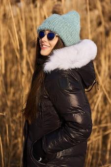 Retrato de mujer joven feliz divertirse en el hermoso día soleado de invierno sobre un fondo de caña