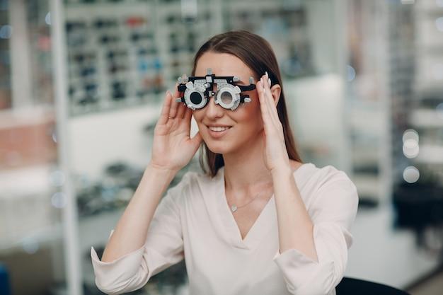 Retrato de mujer joven feliz durante el examen de la vista con gafas de prueba en el óptico optometrista