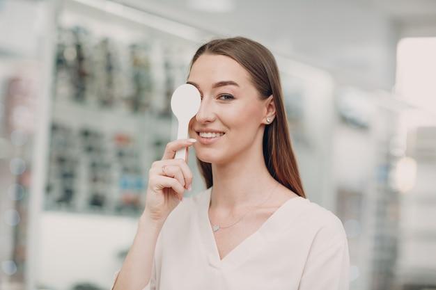 Retrato de mujer joven feliz durante el examen de la vista en el óptico optometrista