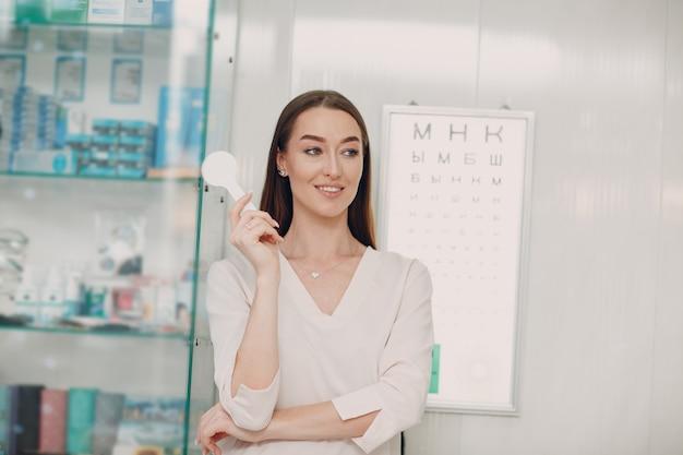 Retrato de mujer joven feliz durante el examen de la vista en el óptico optometrista.