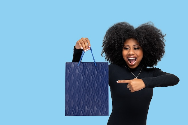 Retrato de una mujer joven feliz con gran sonrisa sosteniendo bolsa de compras aislado sobre fondo azul.