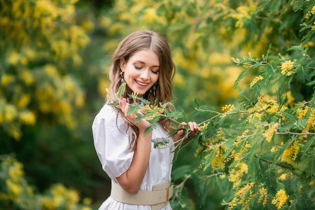 Retrato de una mujer joven feliz con una mimosa.
