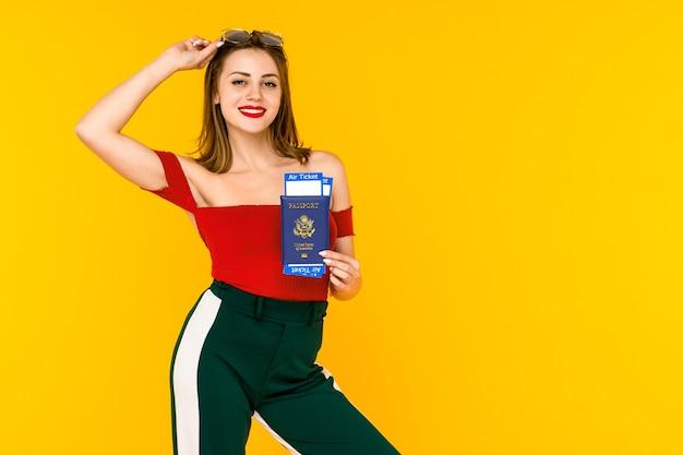 Retrato de una mujer joven feliz con pasaporte y billetes de viaje