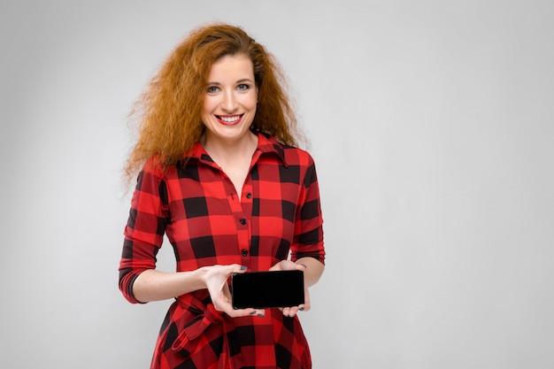 Retrato de la mujer joven feliz del pelirrojo hermoso en vestido a cuadros que sonríe mostrando el teléfono móvil