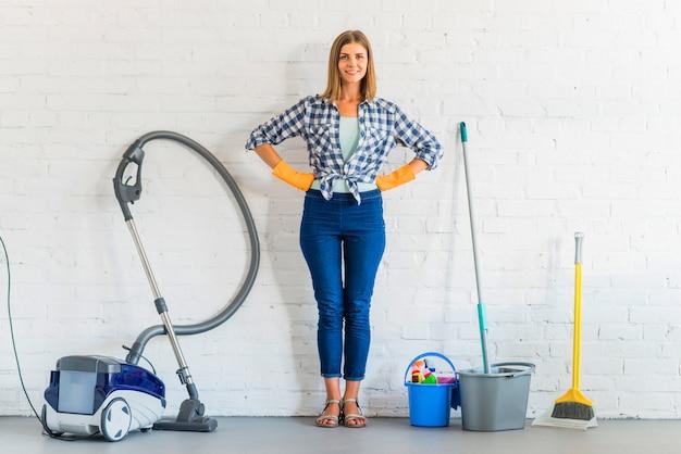 Retrato de una mujer joven feliz de pie delante de la pared de ladrillo con equipos de limpieza