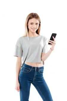 Retrato de una mujer joven feliz de pie y sosteniendo el teléfono móvil