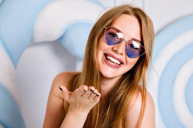 Retrato de mujer joven feliz posando en el estudio cerca de caramelos enormes, pelos largos y sonrisa de belleza de cerca, con gafas de sol y relojes de corazón, estilo pop.