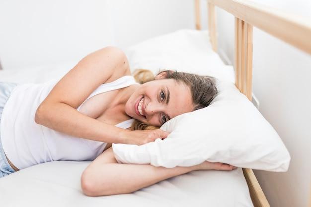 Retrato de una mujer joven feliz que miente en cama