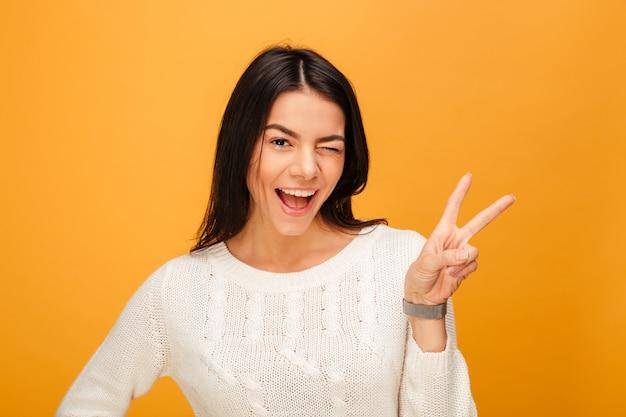 Retrato de una mujer joven feliz que muestra el signo de la victoria
