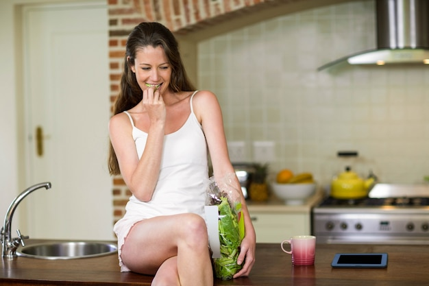 Retrato de la mujer joven feliz que sienta y que come la verdura en encimera de la cocina
