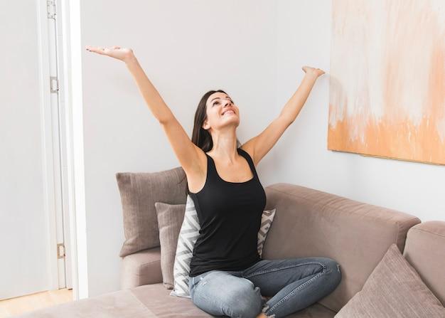 Retrato de una mujer joven feliz que se sienta en el sofá que levanta sus manos que miran para arriba