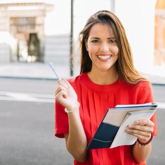 Retrato de una mujer joven feliz que sostiene el diario