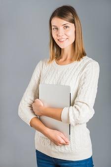 Retrato de una mujer joven feliz que sostiene el ordenador portátil en fondo gris