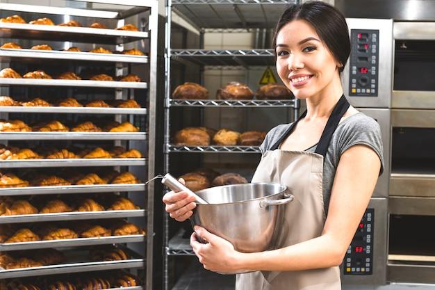 Retrato de una mujer joven feliz que sostiene el tazón de fuente de mezcla delante de estantes cocidos croissant