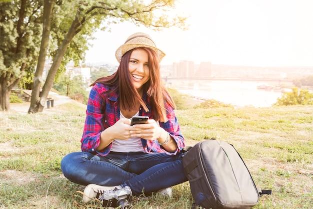 Retrato de una mujer joven feliz que sostiene el teléfono móvil en parque