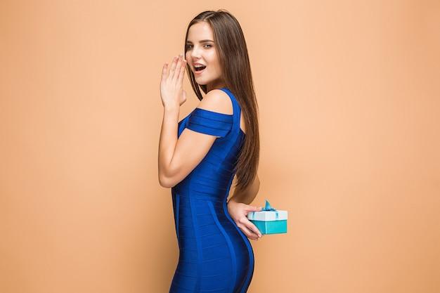 Retrato de mujer joven feliz sosteniendo un regalo aislado en la pared marrón con emociones felices