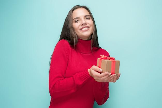 Retrato de mujer joven feliz sosteniendo un regalo