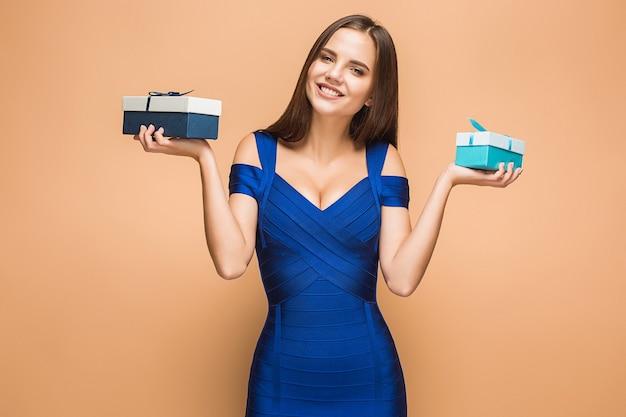 Retrato de mujer joven feliz sosteniendo regalos en marrón