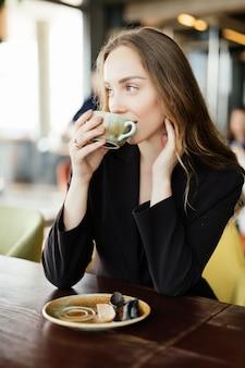 Retrato de mujer joven feliz con taza en manos bebiendo café por la mañana en el restaurante