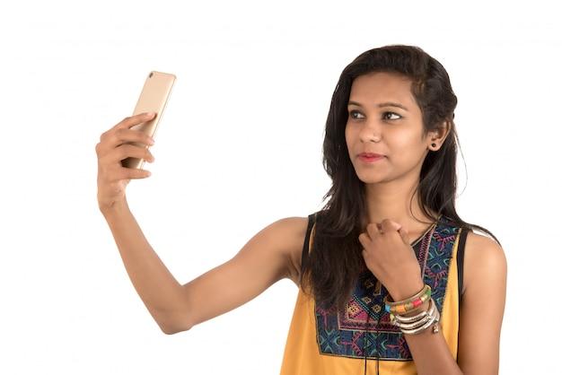 Retrato de una mujer joven feliz con teléfono móvil aislado en blanco