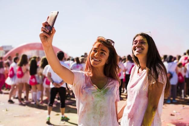 Retrato de una mujer joven feliz tomando selfie en el teléfono móvil durante el festival holi