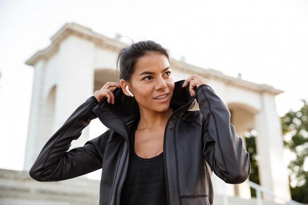 Retrato de una mujer joven fitness en auriculares
