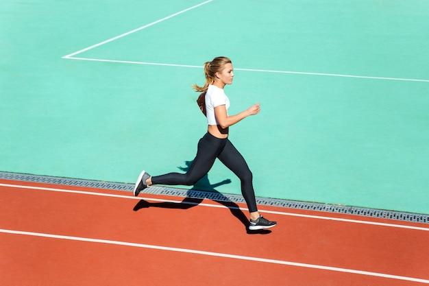 Retrato de una mujer joven fitness corriendo en el estadio
