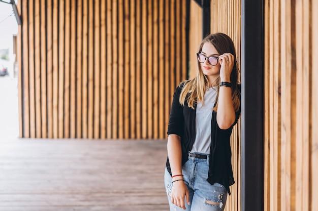 Retrato de una mujer joven en el fondo de madera con tablas verticales. hermosa chica con cabello largo y gafas sonriendo