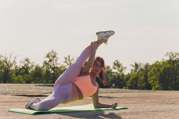 Retrato de mujer joven en forma y deportiva haciendo estiramientos en la ciudad.