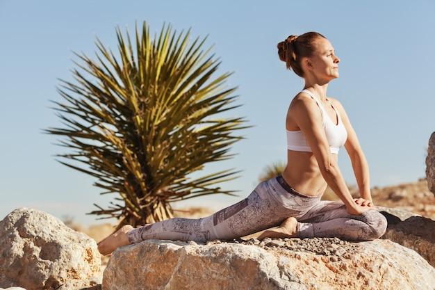 Retrato de mujer joven en forma haciendo yoga en deseert estilo de vida disciplinado al aire libre