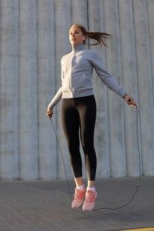 Retrato de mujer joven en forma con saltar la cuerda al aire libre. fitness femenino haciendo ejercicios de salto al aire libre al amanecer o al atardecer.