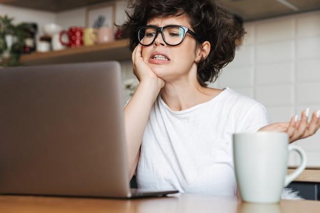 Retrato de una mujer joven frustrada con anteojos trabajando en la computadora portátil en casa por la mañana