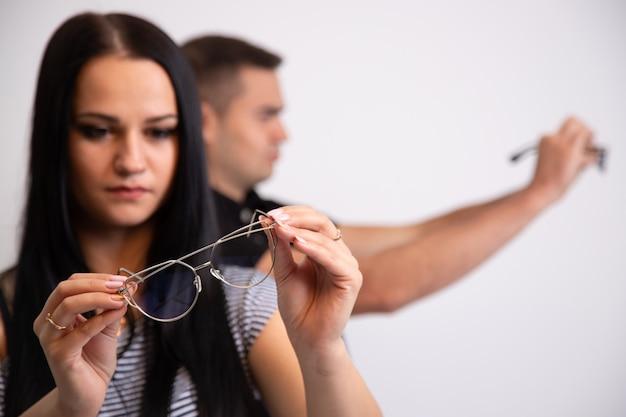Retrato de una mujer joven con gafas en las manos. hombre borroso en el fondo. chica mira a través de las lentes. chica hermosa morena de pelo largo y anteojos en las manos. de cerca.