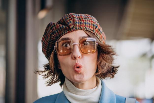 Retrato de una mujer joven con gafas de sol y sombrero