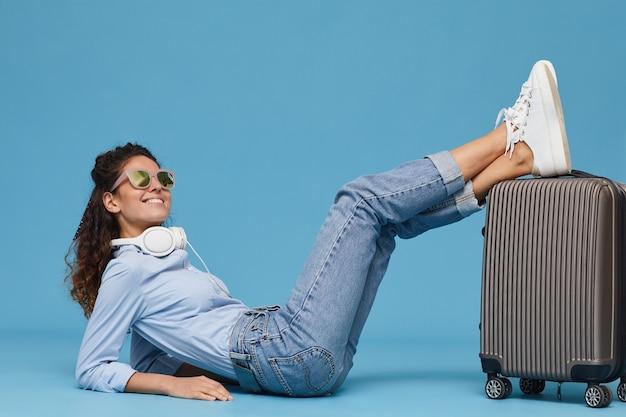 Retrato de mujer joven con gafas de sol tirado en el suelo con equipaje aislado sobre fondo azul.
