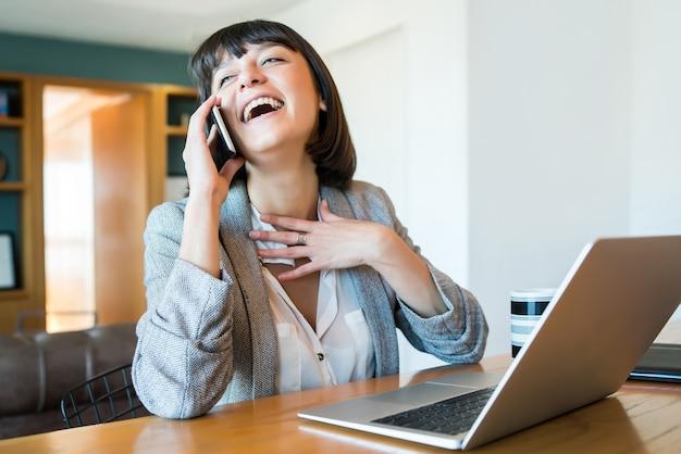 Retrato de mujer joven hablando por su teléfono móvil y trabajando desde casa con el portátil. concepto de oficina en casa