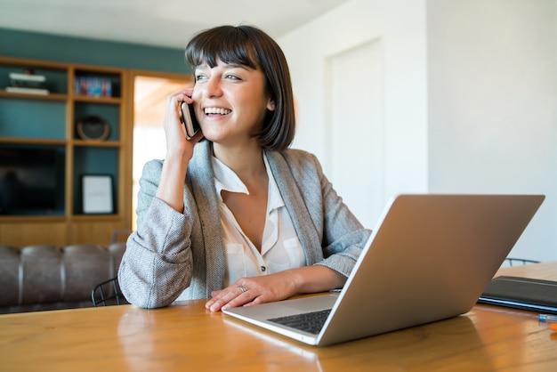 Retrato de mujer joven hablando por su teléfono móvil y trabajando desde casa con un portátil
