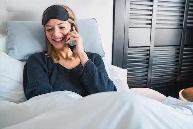Retrato de mujer joven hablando por teléfono mientras está acostado en la cama en la habitación del hotel. concepto de viajes y estilo de vida.