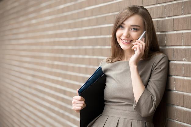 Retrato de mujer joven hablando por teléfono y mirando la cámara en la calle