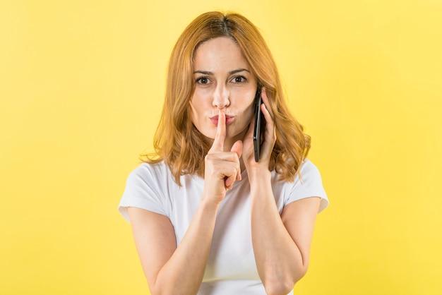 Retrato de una mujer joven hablando por teléfono móvil colocando un dedo sobre los labios mirando a la cámara