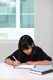 Retrato de mujer joven haciendo los deberes en tableta digital en casa. educación en línea, aprendizaje en casa, concepto de educación en el hogar.