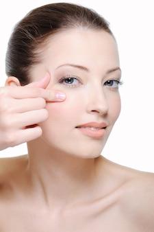 Retrato de mujer joven haciendo pliegue cerca de su ojo