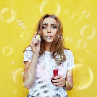 Retrato de mujer joven haciendo pompas de jabón