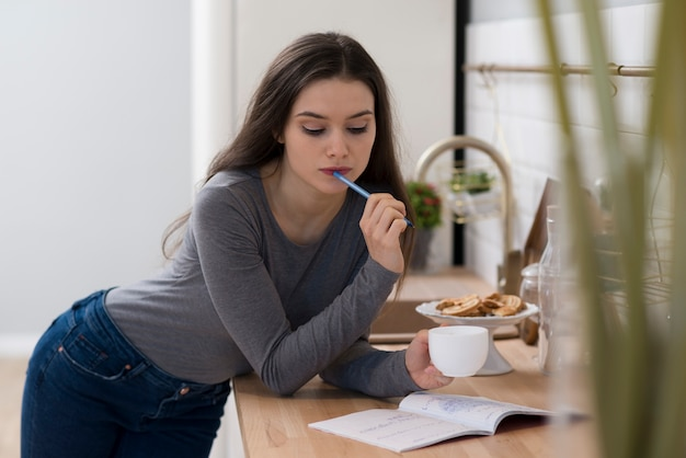Retrato de mujer joven haciendo la tarea mientras toma un café